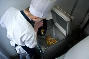 Kok hælder mad i madkværn - BioTrans Nordic